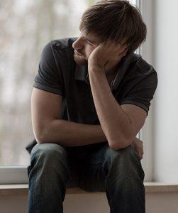 Een jonge man zit op een vensterbank, leunt met zijn hoofd op zijn hand en kijkt schuin voor zich uit.