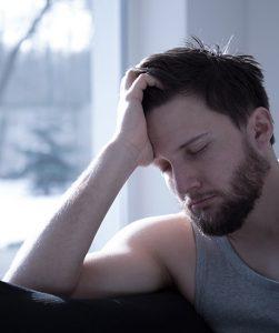 Een jonge man zit met zijn ogen dicht, te slapen wellicht, met zijn hoofd geleund op zijn hand.