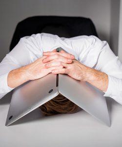 Een man ligt met zijn hoofd op tafel, zijn hoofd ligt onder een opengeslagen laptop, zijn handen zijn over de laptop gelegd..
