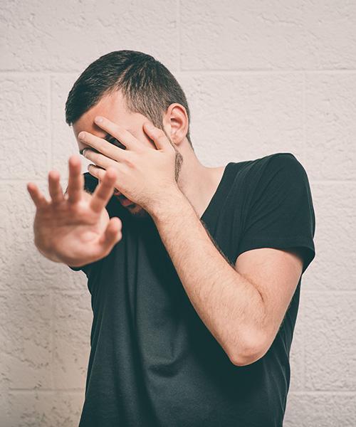 Een man staat voor een witte muur, hij maakt een angstige indruk, verstopt zich achter zijn hand, spiekt tussen zijn vingers door en steekt zijn andere hand afwerend voor zich uit.
