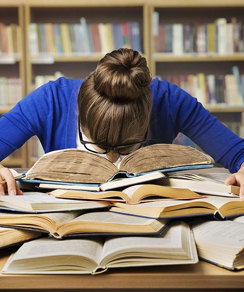 Een jonge vrouw zit in een bibliotheek. Haar hoofd ligt op een stapel boeken die opengeslagen voor haar liggen.