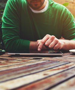 Een man die aan een tuintafel zit, gebruik makend van een tablet. Zijn gezicht is net niet zichtbaar.